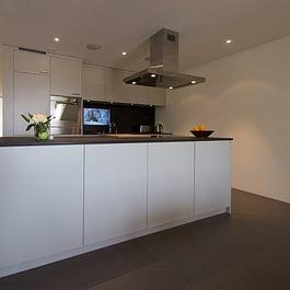 Küche mit Kochinsel und TV in der Glasrückwand