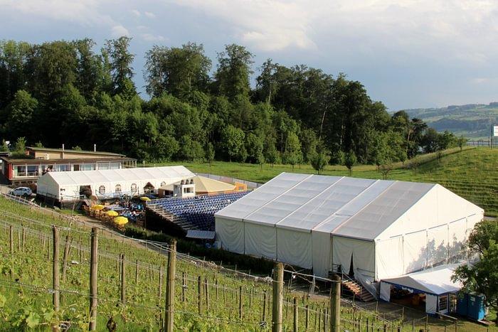 Open-Air Event mit gedeckter Bühne, Tribüne, Plattformen und Zelten.