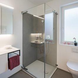 Die großformatigen Keramikplatten bieten eine Dusche ohne Zementfugen. Die grossen Glasflächen mit flächenbündigen Befestigungspunkten runden den eleganten und pflegeleichten Duschbereich ab.