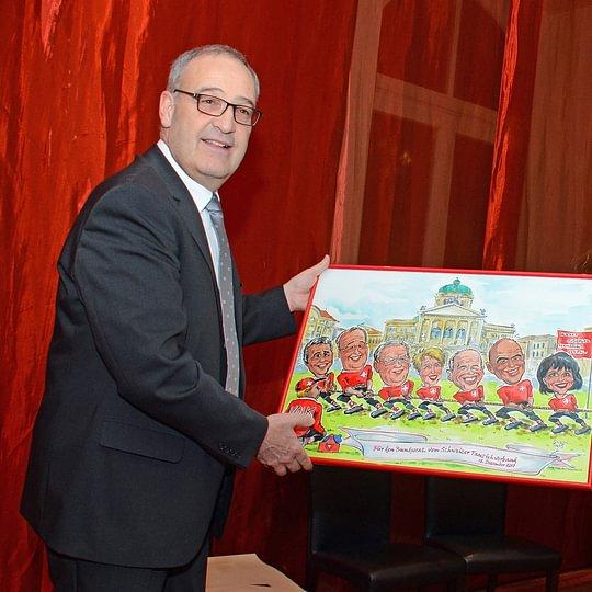 Bundesrat Parmelin erhält ein Cartoongemälde vom Bundesrat und Bundeshaus, überreicht vom Schweizer Tauziehverband