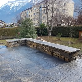 Platz mit Natursteinplatten / Trockenmauer zum sitzen