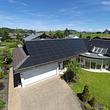 Einfamilienhaus mit rahmenloser, vollflächiger Solaranlage