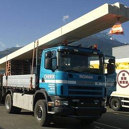 Transport et mise en place de charpente avec camion et remorque surbaissée