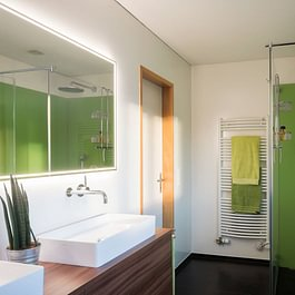 Mit den grünen Glasrückwänden und den holzfarbigen Waschtischunterbauten ist ein perfektes Frühlingsbad entstanden.