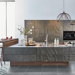 Stone Küche: Die Korrespondenz des schimmernden, echten Steins mit der nur 4mm starken Edelstahlplatte und den Applikationen in Nussbaumholz ergeben einen harmonischen Dialog aus echten Materialien.